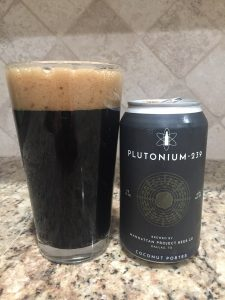 A dark coconut porter beer sitting next to teh can it was poured from.  The can is dark grey labeled Plutonium 239