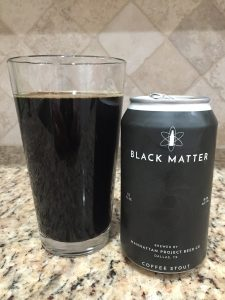 A pint glass of dark beer sits next to a can of displaying the name Black Matter Coffee Stout.  The can is black and the lettering is silver.
