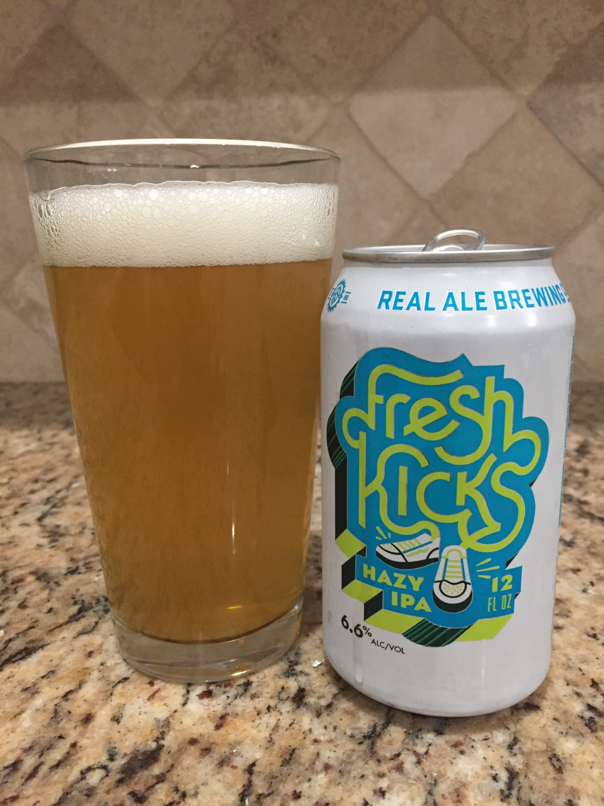 A white 10oz can with Fresh Kicks printed on it sitting next to a 12 oz pint glass of the Fresh kicks Hazy IPA