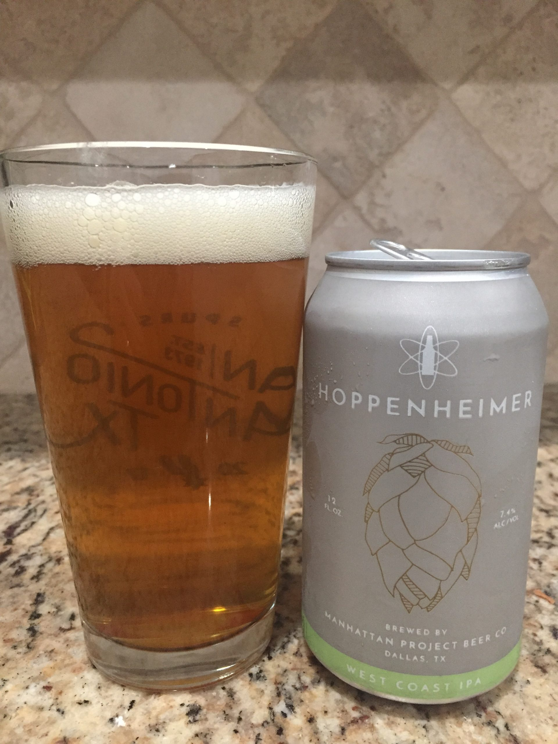 A can of Hoppenhimer IPA from Manhattan Project Beer company is next to a pint glass filled with the golden hazy beer.