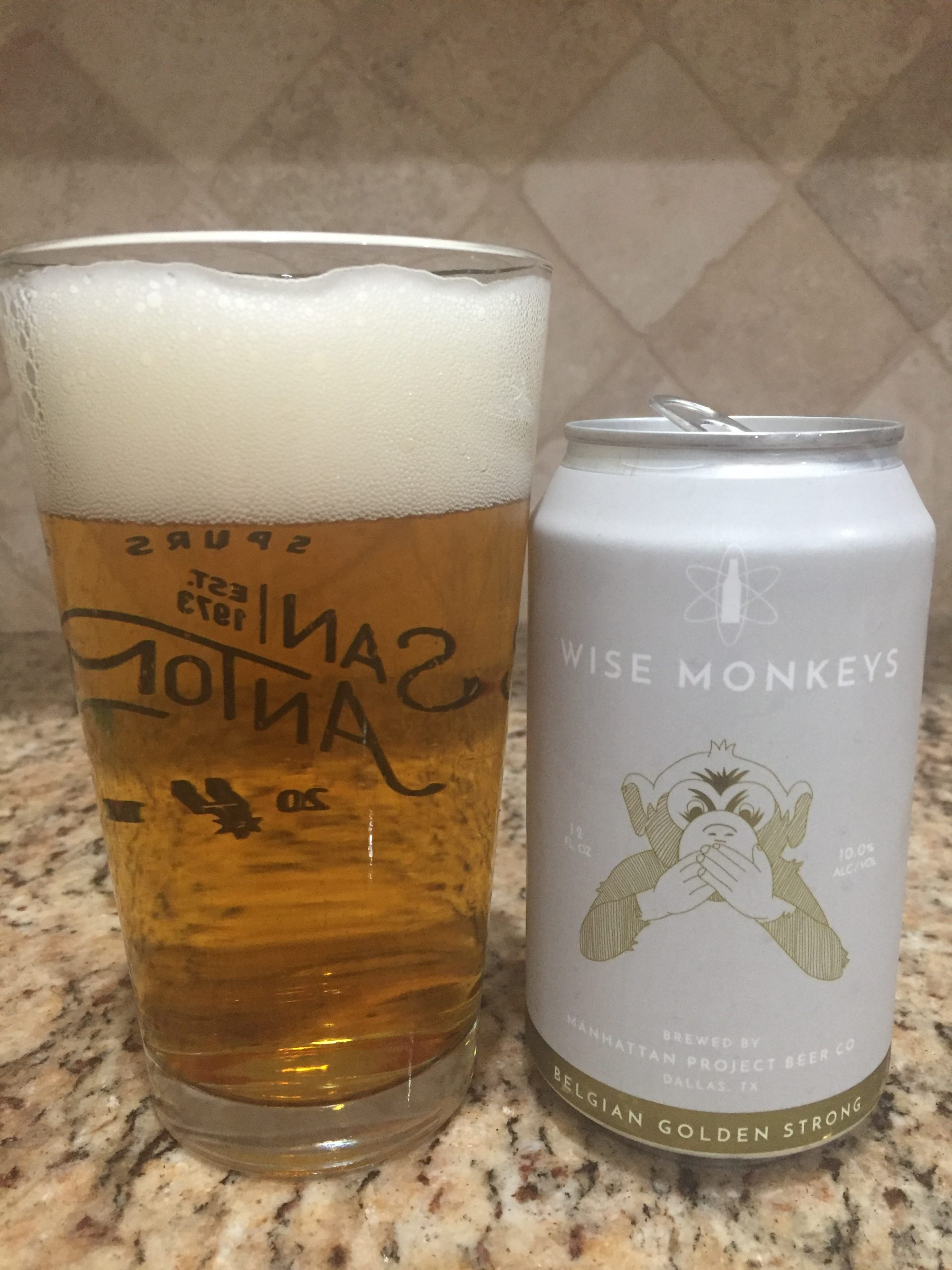 A can of Wise Monkeys from Manhattan Project Beer company is next to a pint glass filled with a clear golden beer with a thick white head.
