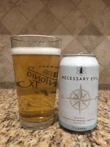 A can of Necessary Evil Pilsner from Manhattan Project Beer Company is next to a pint glass filled with a clear golden yellow beer with one-inch of the white head floating on top.