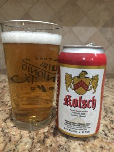 A can of Kolsch beer from Altstadt Brewery is next to a pint glass filled with a clear golden beer with small white head floating on top.