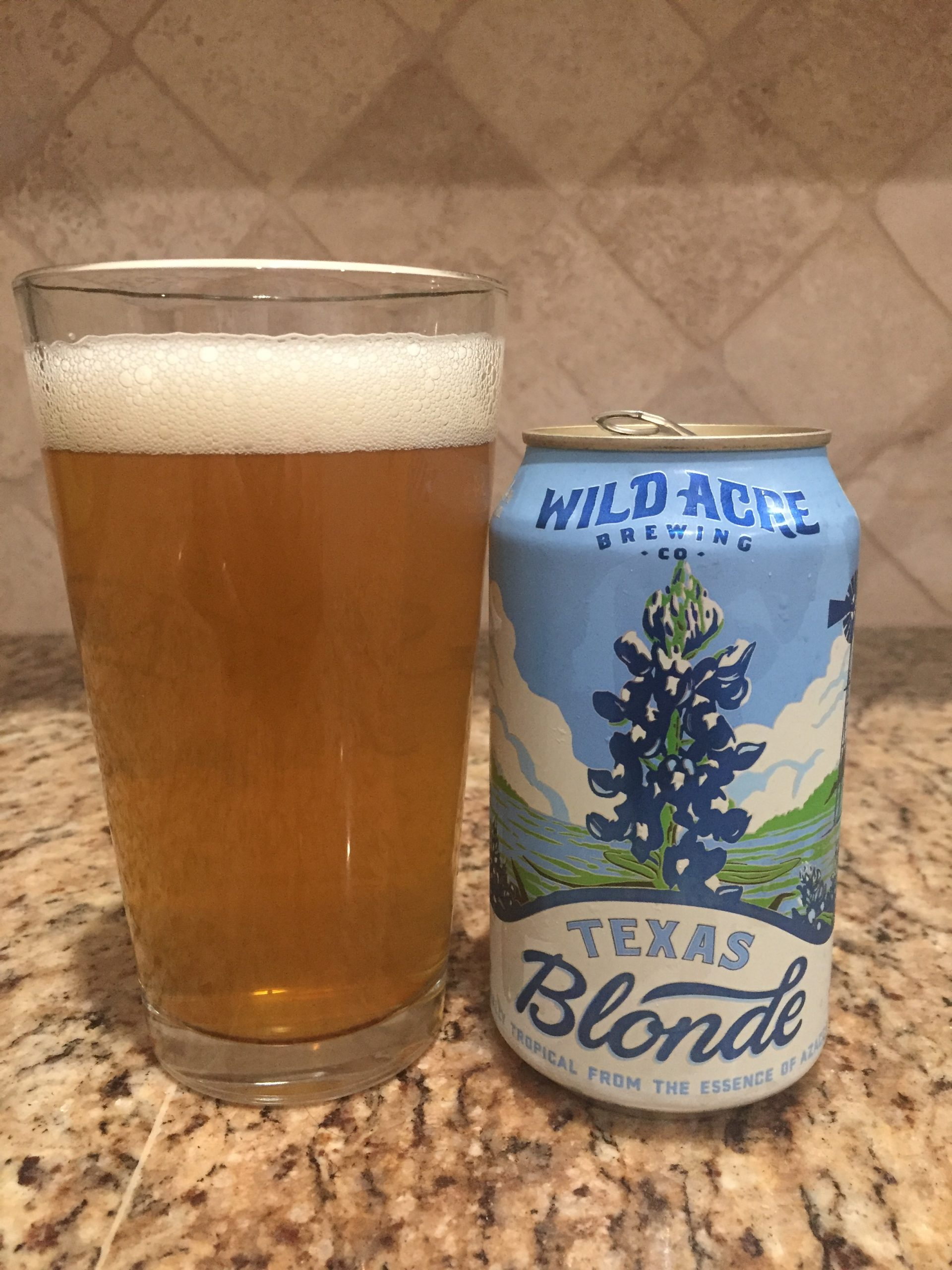 A 12 oz can of Texas blond from Wild Acre Brewing Company sits next to a pint glass full of a brassy golden beer with a one finger head.