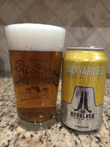 A can of Backyard Bee, from Revolver Brewing, is next to a pint glass filled with a clear golden beer with a thick head floating on top.