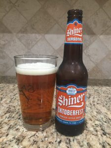 A can of Hefe, a Shiner Oktoberfest beer from Spoetzl Brewery is next to a pint glass filled with a clear amber-orange beer with small white head floating on top.