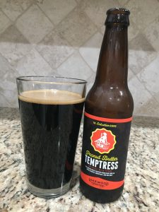 A bottle of Peanutbutter Tempterest, from Lakewood Brewing, is next to a pint glass filled with a Dark beer with almost no head floating on top.