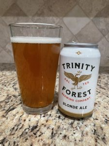 A can of Blonde Ale from Trinity Forest Brewing Company is next to a pint glass filled with a clear golden beer with a thin head floating on top.