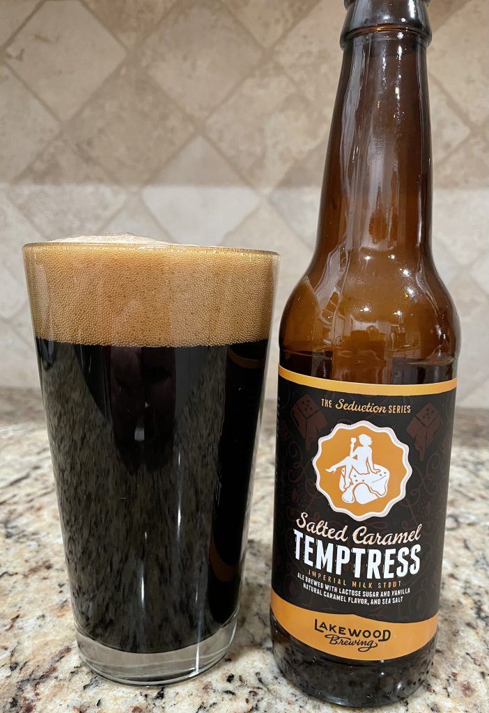 A bottle of Salted Caramel Tempterest, from Lakewood Brewing, is next to a pint glass filled with a Dark beer with a dark almond head floating on top.