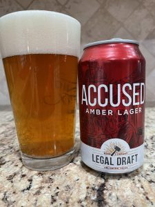 A can of Accused Amber lager from Legal Draft Beer Company is next to a pint glass filled with a clear amber golden beer with a thick head floating on top.