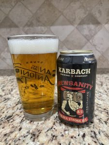 A can of Brewsanity from Karbach Brewing Company is next to a pint glass filled with a dark golden beer with a thick head floating on top.