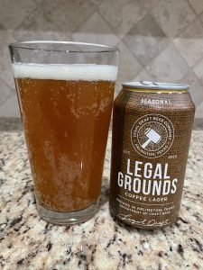 A can of Legal Grounds from Legal Draft Brewing Company is next to a pint glass filled with a dark golden beer with a thick head floating on top.