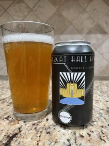 A can of Great hall Hefe from Pegasus City Brewery is next to a pint glass filled with a dark golden amber beer with a white head floating on top