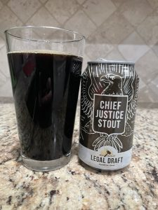 A can of Chief Justice Stout from Legal Draft Beer Company is next to a pint glass filled with a dark brown beer with almost no head floating on top.