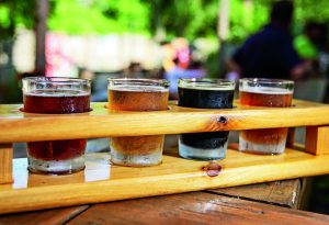 A flight of 4 Beers in a wooden rack.