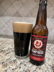A bottle of French Toast Tempterest, from Lakewood Brewing, is next to a pint glass filled with a Dark beer with a dark almond head floating on top.