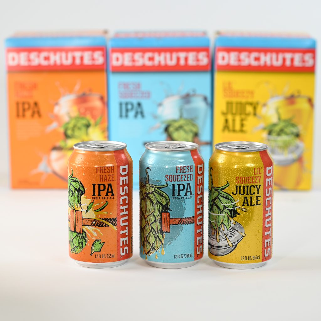 Three cans of beer from the Fresh Family from Deschutes Brewery sit in front of there packaging.