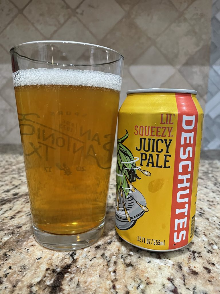 A can of Lil Squeezy Juicy pale from Deschutes Brewing Company is next to a pint glass filled with a golden beer with a white head floating on top.