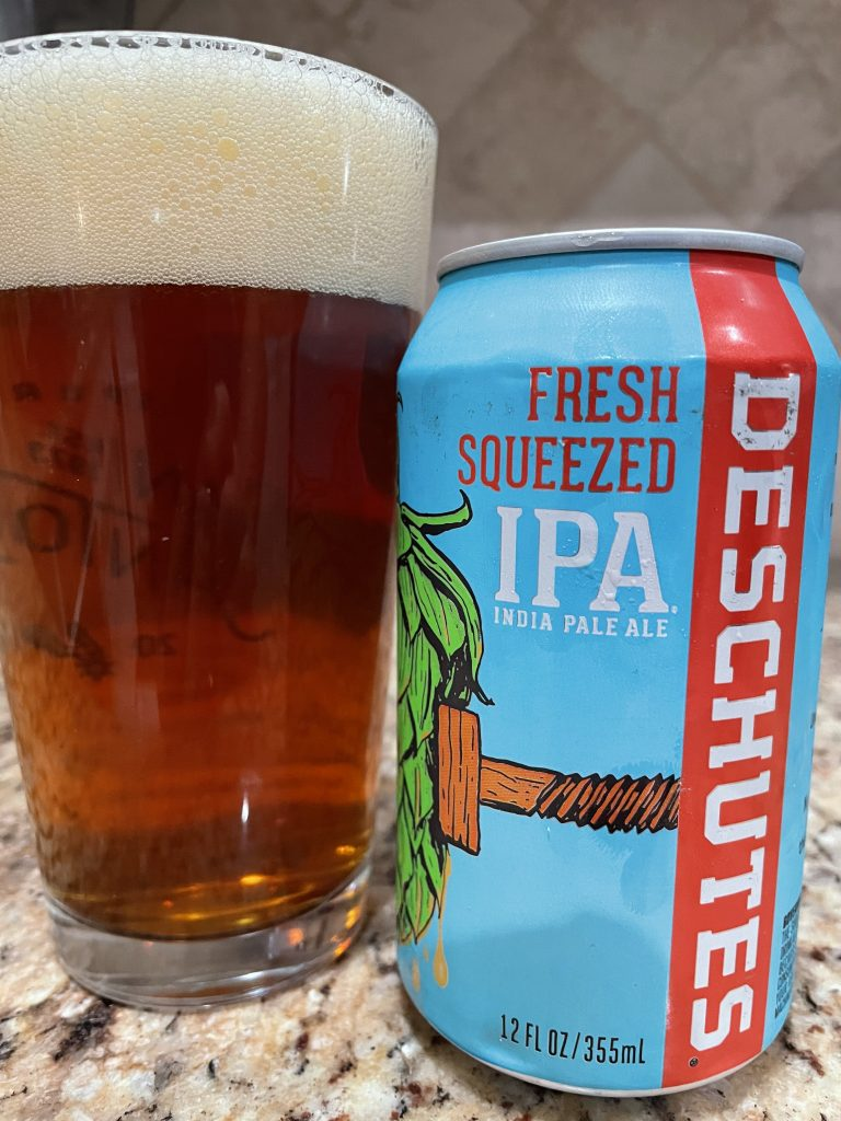A can of Fresh Squeezed IPA from Deschutes Brewing Company is next to a pint glass filled with a dark red amber beer with a white head floating on top