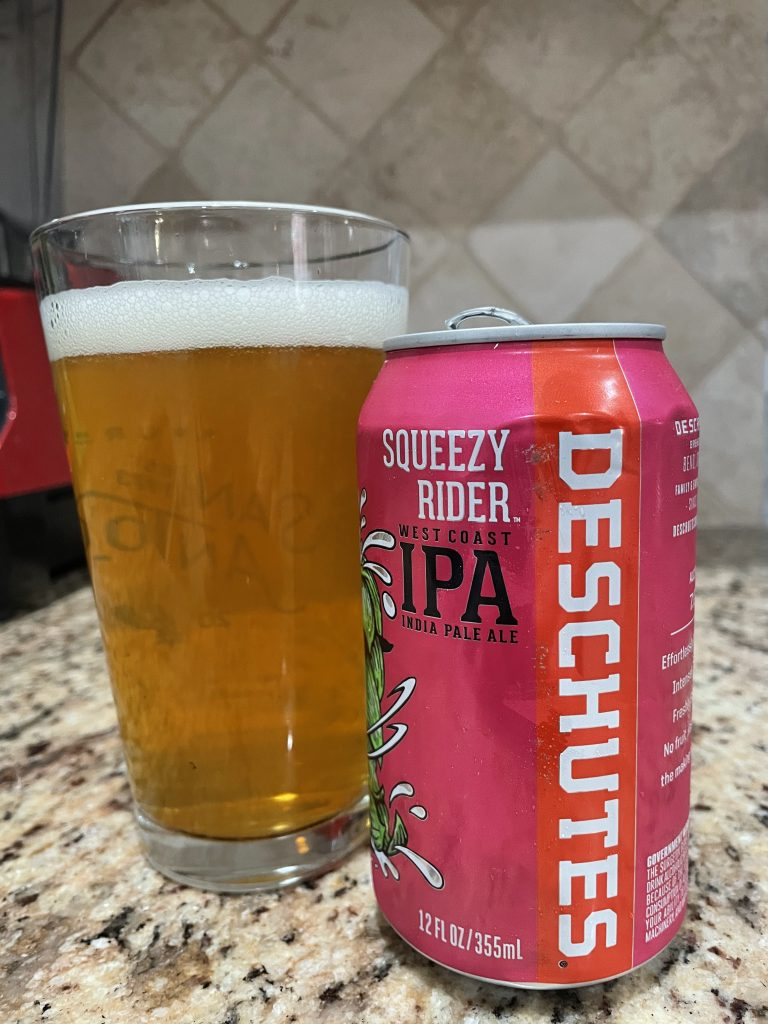 A can of Squeezy Rider IPA from Deschutes Brewing Company is next to a pint glass filled with a dark golden beer with a white head floating on top.