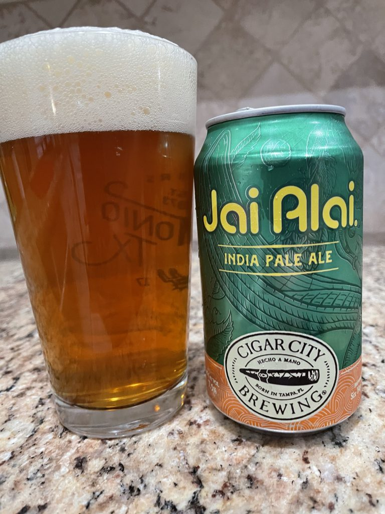 A can of Jai Alai from Cigar City Brewing is next to a pint glass filled with a  golden beer with a white head floating on top.